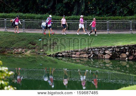 KUALA LUMPUR, MALAYSIA - OCTOBER 29, 2016: Golfers walk along the lake towards the 18th hole of the TPC Golf Course during the 2016 Sime Darby LPGA Malaysia golf tournament.