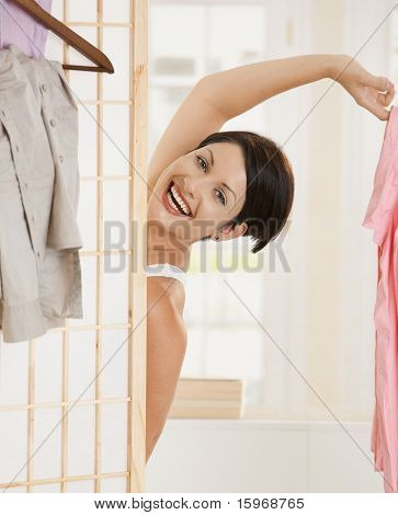 Happy young woman undressing, looking out beckoning behind dressing panel, holding pink shirt.?
