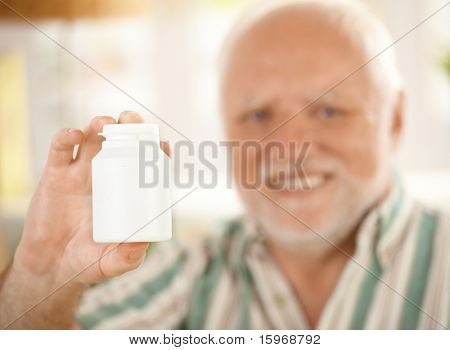 Blank medicine phial in focus handheld by elderly smiling man, copyspace.?