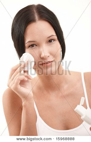 Beautiful young woman cleaning face with cotton pad and makeup removal, looking at camera.?