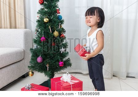 Asian Chinese little girl holding gift box crying beside Christmas tree in the living room at home.