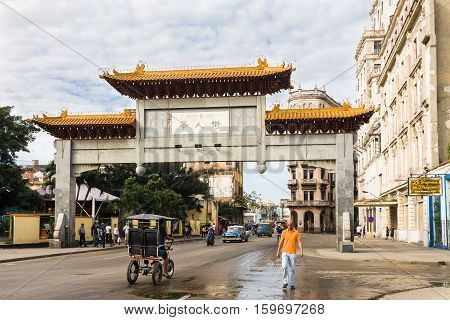 Havana Cuba - 2012 December 10 : The chinese arch or gate which is the entrance to the Cuban Chinatown or Barrio Chino in the center of Havana with traffic and people on the street Cuba