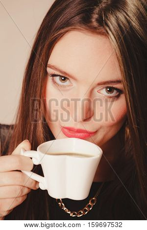 Break and relax time. Elegant beauty woman in black dress holding and drinking hot fresh coffee in white heart shaped cup mug.