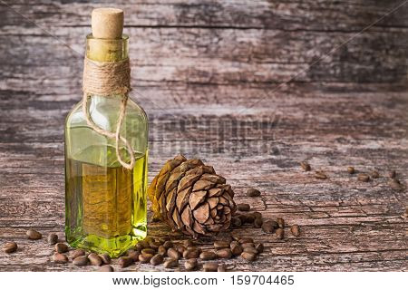 Cedar oil in a glass bottle and a cedar cones with nuts on a brown wooden background.