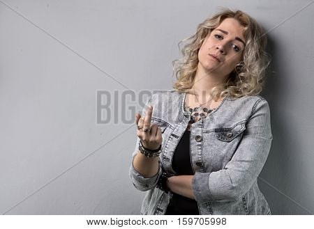 Sad blond woman with middle finger on white background