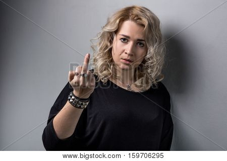 Sad blond woman showing middle finger on white background