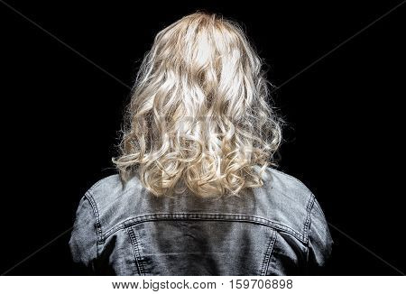 Woman's back and jeans jacket on black background