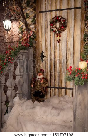 New Year's porch decorated with Christmas wreath snow and toy gnome. Wooden door closed