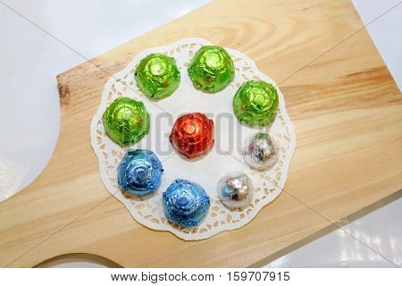 Home made chocolate ball praline colorful pack on wooden board