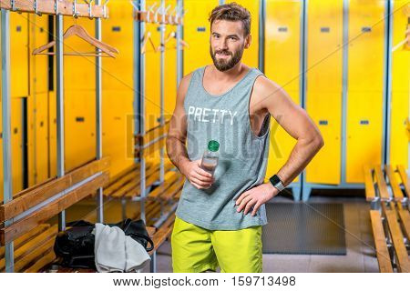 Sports man standing with bottle of water in the locker room at the gym. Drinking water after the training