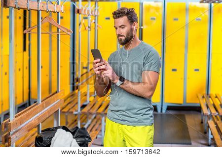 Handsome sports man listening to the music with smart phone in the locker room at the gym