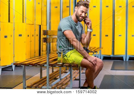 Handsome sports man talking with phone sitting in the locker room at the gym