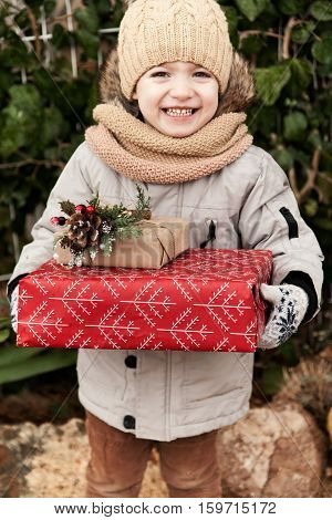 Little Boy In Winter On The Street With Gifts In Hands