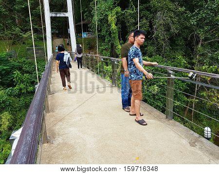 KANCHANABURI THAILAND - NOVEMBER 26: unidentified asian tourists walking on the suspension bridge for pedestrians crossing the River Kwai at Sai Yok National Park on November 26 2016 in Kanchanaburi Thailand