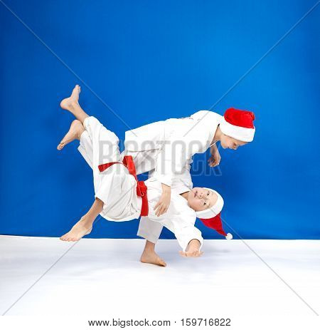 On a blue background two athletes train judo throws
