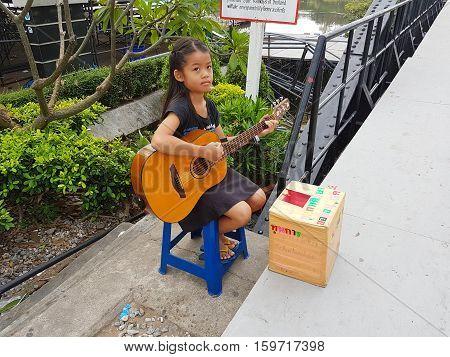KANCHANABURI THAILAND - NOVEMBER 26: unidentified asian girl playing guitar for donating on Bridge on the river Kwai on November 26 2016 in Kanchanaburi Thailand