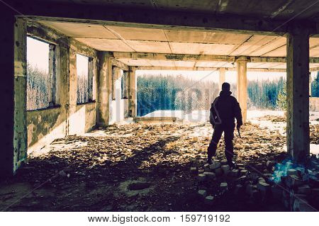 man in uniform with a gun in the ruins on the background of bright lights
