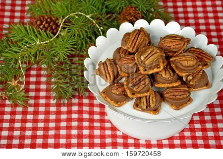 melted chocolate candy on pretzel with Christmas pine bough