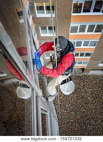 worker washes windows cleans on a rope