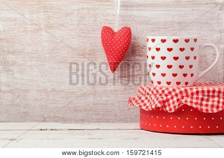 Valentine's day background with coffee cup and heart shape on wooden table