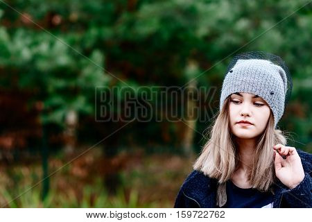 Thoughtful Young Woman In Woolen Grey Cap