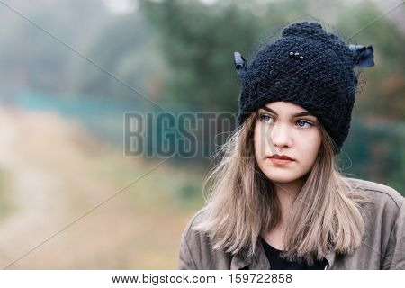 Thoughtful Young Woman In Black Woolen Cap