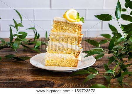 Piece of biscuit layered cake with cream cheese and lemon curd decorated with fresh mint leaves, physalis, lemon slices and green grapes on a plate, selective focus