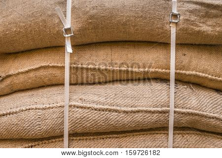 Background of stacked burlap sacks  - Close-up image of jute sacks filled with goods piled upon each other and tied up ready for transportation.