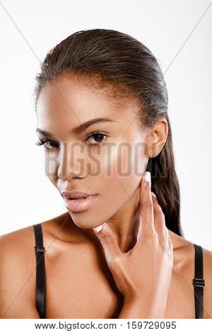 Pure seduction. Young mulatto lady is standing and posing isolated on background