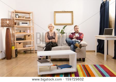 Offended couple man and woman sitting on sofa with their arms folded or crossed. Beautiful couple in love do not speak and looking angry at home. Disappointment concept.