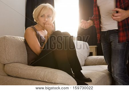 Couple man and woman having conflict concerning family life. Frightened blond lady sitting on sofa or couch and looking away while her husband screaming and explaining her something at home.