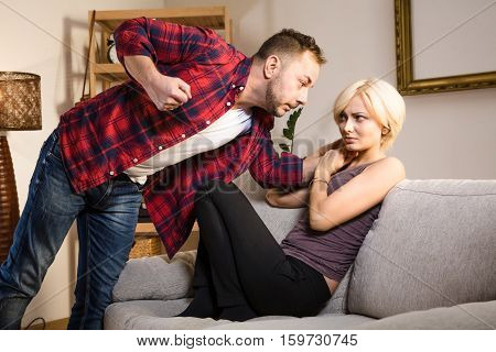 Couple man and woman having conflict and battle at home. Frightened blond lady sitting on sofa or couch and listening to her husband.