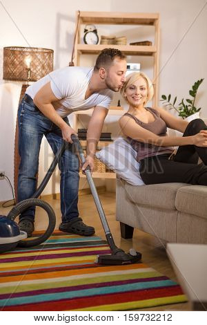 Handsome man using vacuum cleaner and kissing his wife while she is resting and relaxing on sofa or couch at home. Family and household concepts.