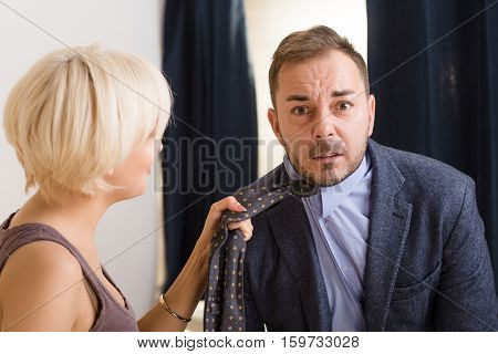 Man under pressure of his angry wife. Blond lady wife keeping her husband's tie and screaming at him. Family concept. Quarrel concept.