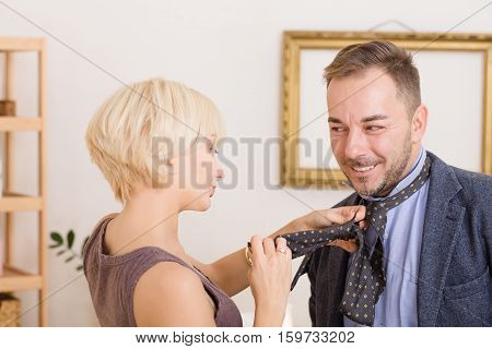 Man under pressure of his wife. Blond lady helping her husband with his tie. Handsome businessman going to work. MArriage concept. Family concept.