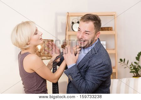 Family concept. Man under pressure of his wife. Blnd lady helping her husband with his tie. Businessman smiling and screaming.