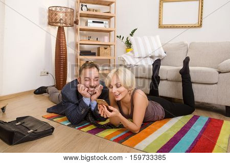 Beautiful couple man and woman lying on floor and smiling for camera. Man and woman looking at smart or mobile phone while resting at home.
