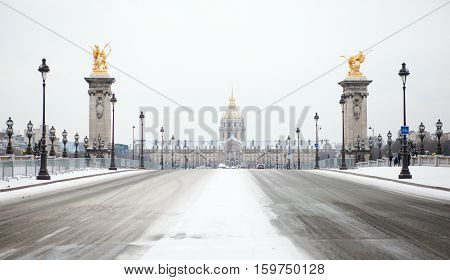 Winter In Paris. Pont Alexandre Iii And Invalides Cathedral Under Snow