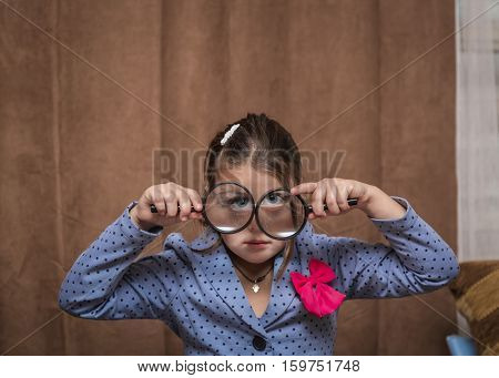 great amazing closeup view of a funny stylish little girl looking trough a magnified glasses against dark brown curtains background