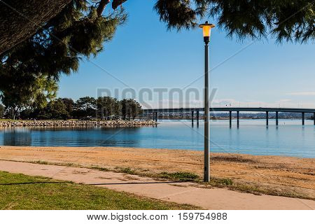 Lamppost at Vacation Isle Park with Mission Bay and Ingraham Street bridge in the background.