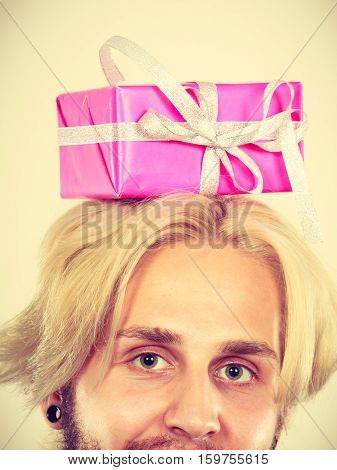 Celebration and giving concept. Young man with pink gift box on his head. Guy have idea for present