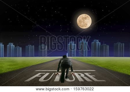 Business man ready to run Future line in front of city. Night back view.