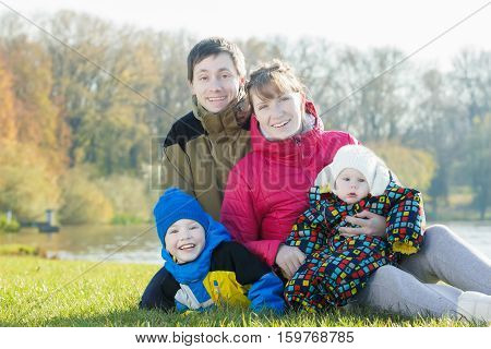 Outdoor family portrait of parents couple with little siblings in park