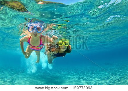 Happy family - mother with baby girl dive underwater with fun in sea pool. Healthy lifestyle active parent people water sport outdoor adventure swimming lessons on beach summer holidays with child