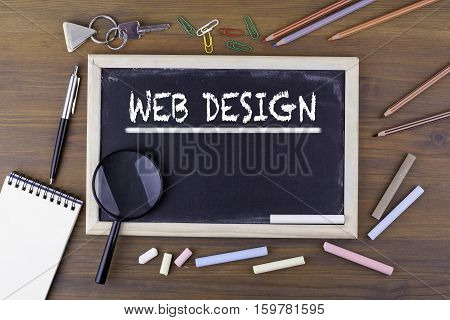Web Design. Text on the chalk board. Wooden table with a magnifying glass and writing utensils.
