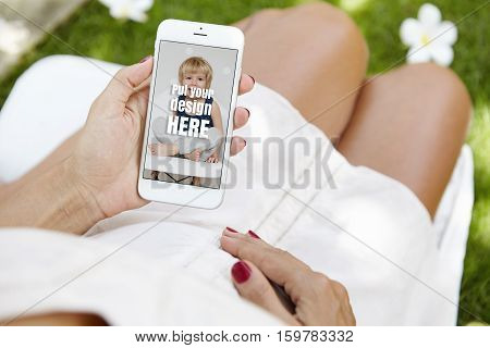 Woman Expecting Baby Sitting On Grass In Park With Electronic Gadget In Her Hands. Pregnant Female I