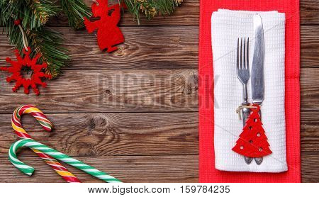 Christmas table place setting with fork and knife, decorated christmas toy - red fir-tree, two lollipop cane and christmas pine branches. Christmas holidays background.