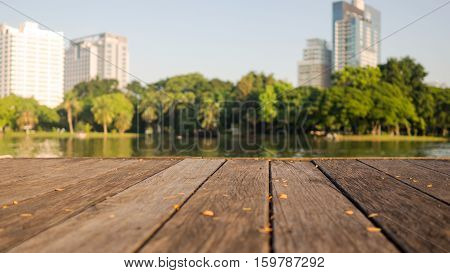 Defocus blur terrace wood and water trees and building inside. Park view in city natural background. Lumpini park Bangkok Thailand.