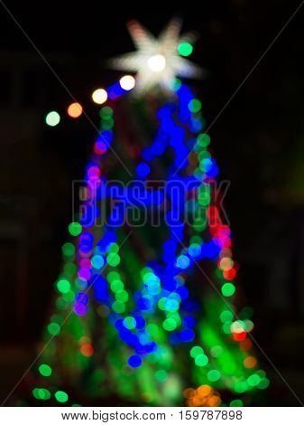 Defocused blur Christmas tree from blue green bokeh abstract lights background.