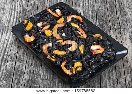 Black Noodles With Prawns And Mussels On Black Rectangular Platter
